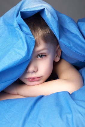 sleepy boy in blue bedclothes